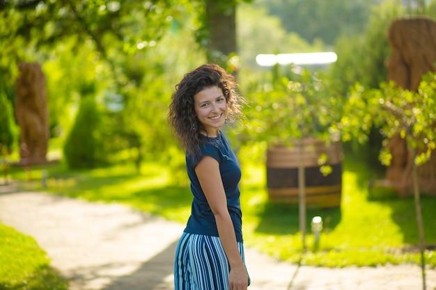젊은 아름 다운 갈색 머리의 초상화는 녹색 공원에서 밝은 여름날을 즐길 수 있습니다.