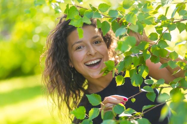 젊은 아름 다운 갈색 머리의 초상화는 녹색 여름 공원에서 산책을 즐길 수 있습니다.