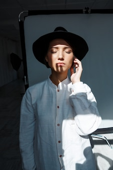 검은 모자에 젊은 아름 다운 갈색 머리 여자의 초상화.