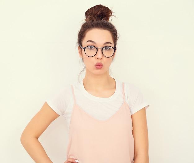壁に近いポーズカラフルな夏ピンクヒップスター服で裸化粧と若い美しいブルネットの女性少女モデルの肖像画。空気キスを与える