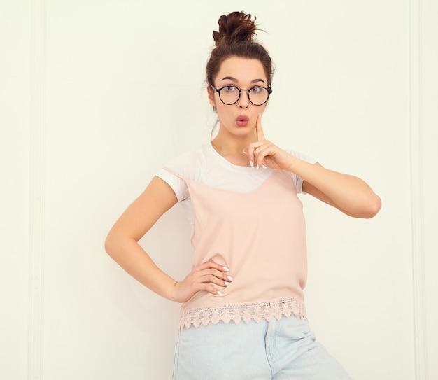 壁に近いポーズカラフルな夏ピンクヒップスター服で裸化粧と若い美しいブルネットの女性少女モデルの肖像画。持っているとアイデア