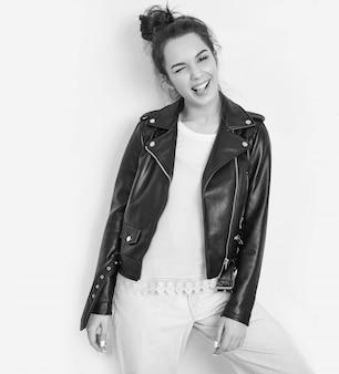 Портрет молодой красивой женщины брюнетка девушка модель с обнаженной макияж носить летние битник байкер кожаная куртка позирует возле стены. подмигивающий