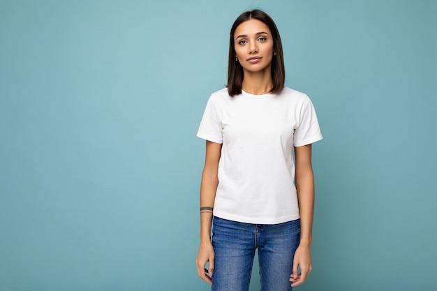 モックアップのための空きスペースとトレンディな白いtシャツを着ている若い美しいブルネットの女性の肖像画