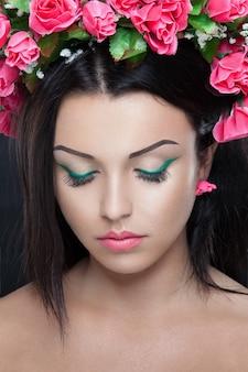 メイクと髪の花を持つ若い美しいブルネットの女性の肖像画