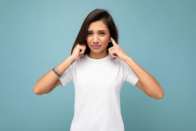 空のスペースと手で耳を覆う青い背景で隔離のモックアップのためのカジュアルな白いtシャツを着て誠実な感情を持つ若い美しいブルネットの女性の肖像画。