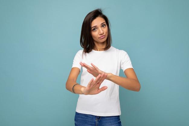 빈 공간과 시간 제한 제스처를 보여주는 파란색 배경에 고립 된 모형에 대 한 최신 유행 흰색 티셔츠를 입고 성실한 감정을 가진 젊은 아름 다운 갈색 머리 여자의 초상화.