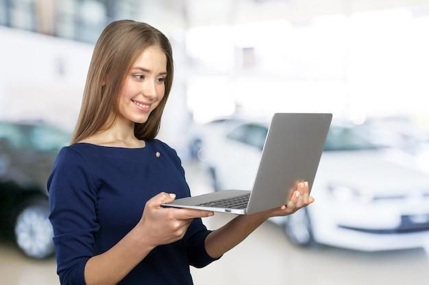 Портрет молодой красивой брюнетки женщины, держащей ноутбук