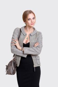 黒のドレス、ジャケット、灰色の背景にバッグと金髪の若い美しいビジネス女性の肖像画