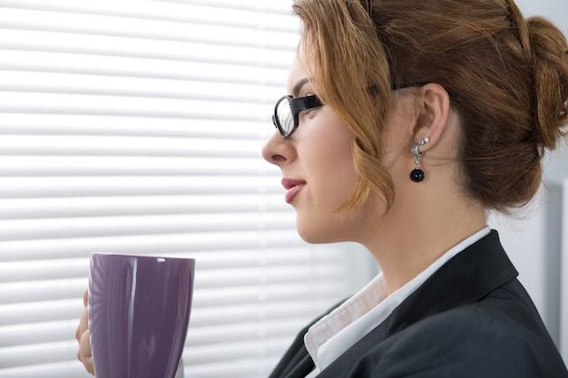 窓の近くに立って、コーヒーブレーク中にお茶のカップで外を見て若い美しいビジネス女性の肖像画