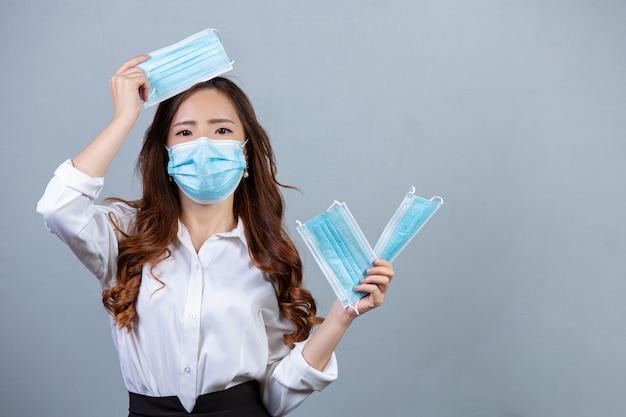 灰色の表面にフェイスマスクを身に着けている若い美しいビジネス女性の肖像画