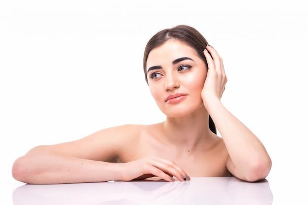 分離された彼女の顔に触れる若い美しい白人女性の肖像画。顔の洗浄、完璧な肌。スキンケア、美容