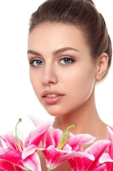 白い背景の上に分離されたピンクのユリと若い美しい白人女性の肖像画