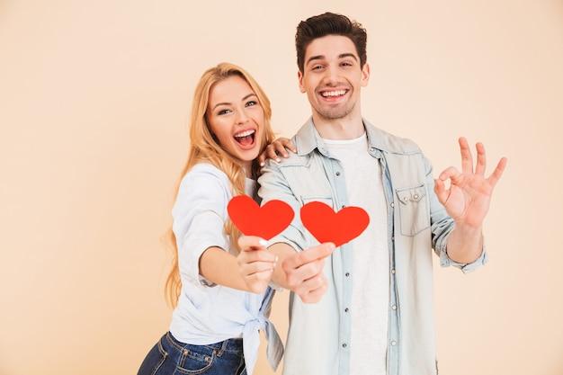 Портрет молодой красивой пары, мужчины и женщины в базовой одежде, держащих красные бумажные сердечки и жестикулирующих знак ок, изолированные на бежевой стене