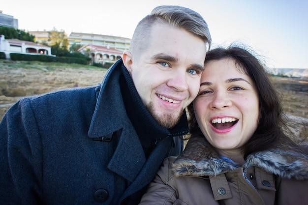 海と暗い曇り空を背景にしたスマートフォンでselfie写真を撮る美しいカップルの肖像画。寒い季節や旅行のコンセプトです。