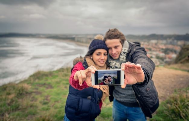 海と暗い曇り空を背景にスマートフォンで自分撮り写真を撮る若い美しいカップルの肖像画。電話に選択的に焦点を当てます。