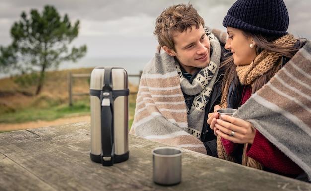 Портрет молодой красивой пары под одеялом с горячим напитком в холодный день с морем и темным облачным небом на заднем плане