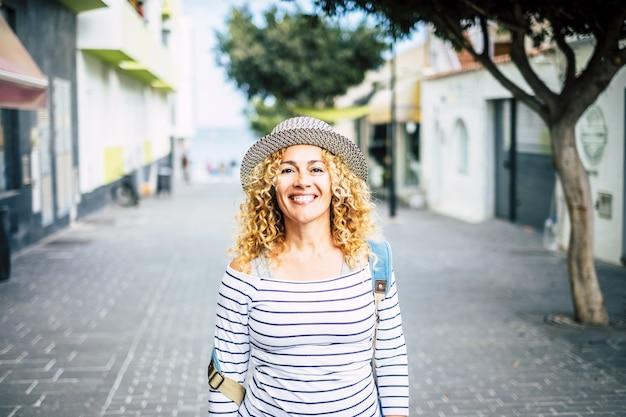 새로운 장소를 발견하고 여행하는 거리를 걷는 동안 카메라를 바라보는 젊은 아름다운 곱슬머리 여성의 초상화