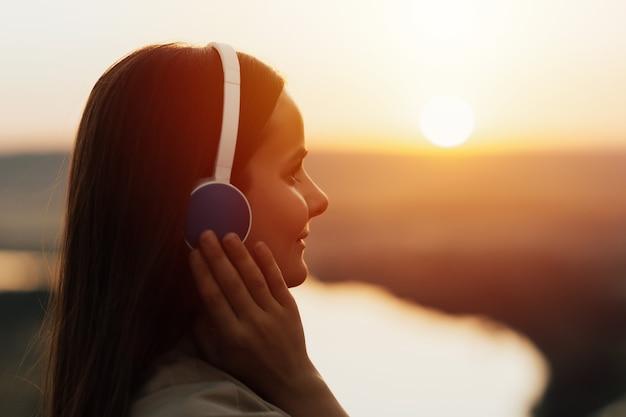 音楽を聞いている屋外で若い美しいかわいい陽気な幸せな笑顔の女の子の肖像画