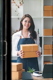 Портрет молодой красивой предпринимательницы, держащей посылочную коробку, стоящую в ее магазине, улыбающуюся и смотрящую в камеру, онлайн-доставка бизнеса