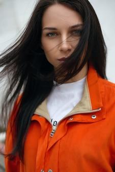 Портрет молодой красивой модной девушки-хипстера в красной летней куртке возле белой стены