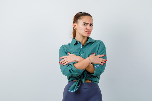 녹색 셔츠에 추위를 느끼고 쾌활한 앞모습을 바라보는 젊은 아름다운 여성의 초상화