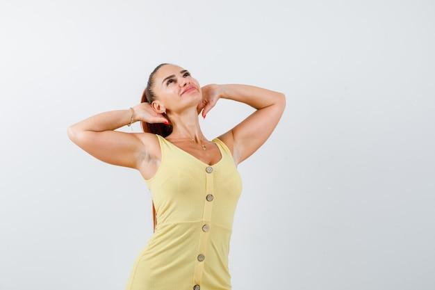 Портрет молодой красивой женщины, держащей руки за головой в платье и выглядящей расслабленным видом спереди