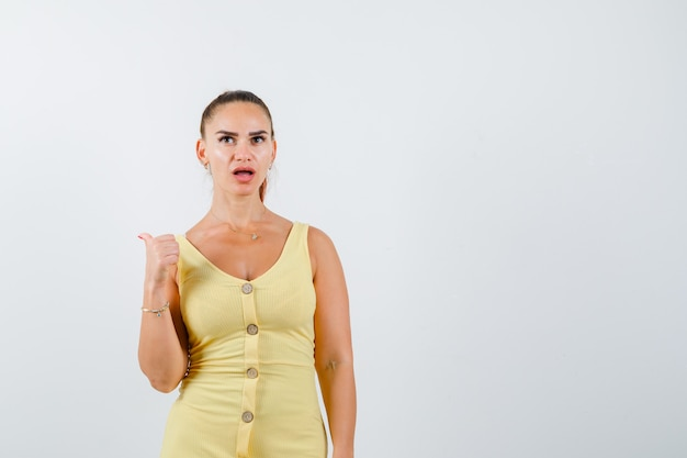 ドレスを着て親指で後ろを向いて困惑した正面図を見て若い美しい女性の肖像画 無料写真