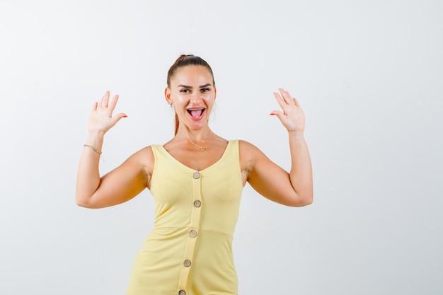 Портрет молодой красивой девушки, показывающей жест капитуляции в платье и выглядящей веселым видом спереди