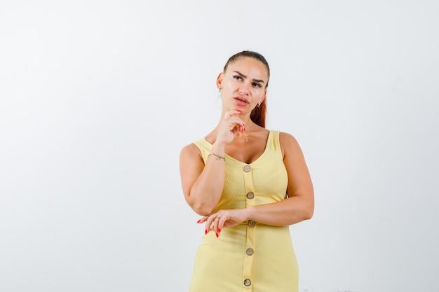 Портрет молодой красивой женщины, стоящей в позе мышления в платье и выглядящей озадаченно, вид спереди