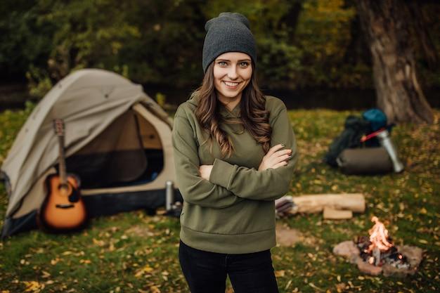 텐트 근처 숲에서 젊은 아름다운 여성 관광객의 초상화