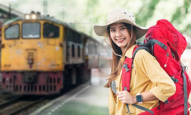 Портрет молодой красивой женщины-путешественницы с рюкзаком в ожидании отправления на вокзале, улыбаясь и глядя вперед