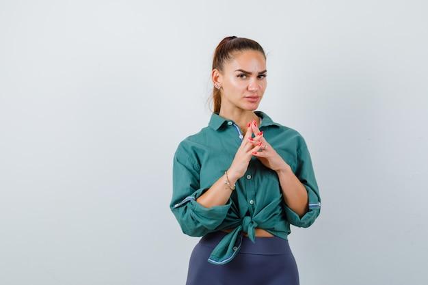 緑のシャツと物思いにふける正面図に絡み合っている指を持つ若い美しい女性の肖像画