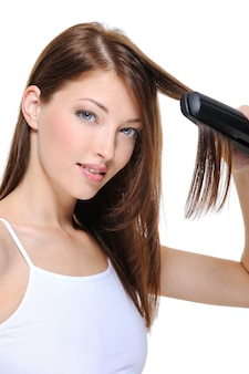 Портрет молодой красивой девушки делает прическу утюгом для волос