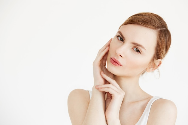 얼굴을 만지고 젊은 아름 다운 여자의 초상화입니다. 페이셜 트리트먼트. 미용 화장품 및 스킨 케어.