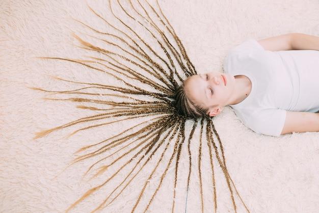 創造的なエレガントな髪型を持つ若い美しい少女の肖像画
