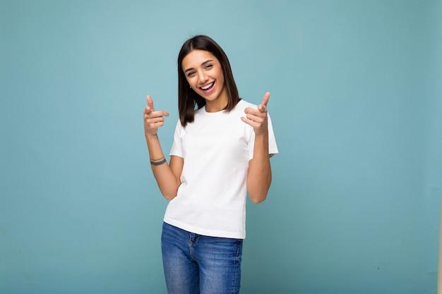 Портрет молодой красивой счастливой улыбающейся брюнетки в модной белой футболке с пустым