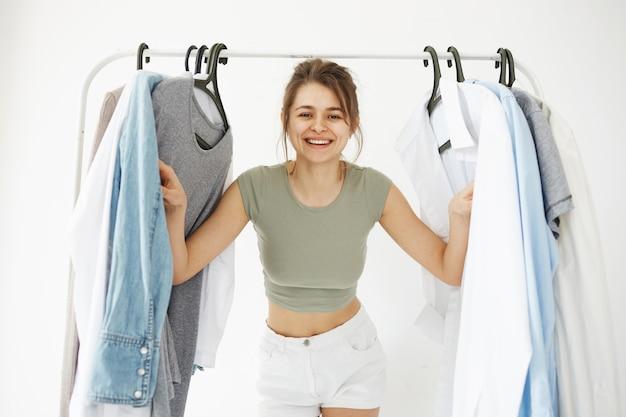 Портрет молодой красивой счастливой женщины смотря наблюдать шкафа вешалок усмехаясь на камере над белой стеной.