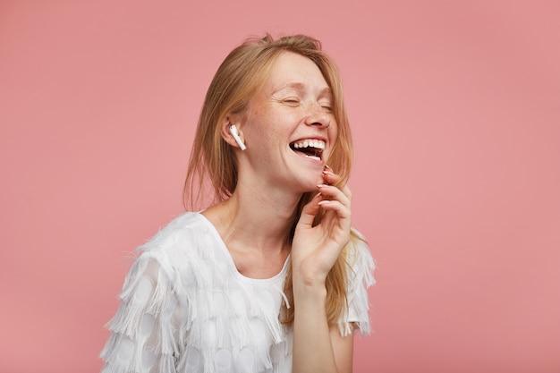 Портрет молодой красивой счастливой женщины с хитрыми волосами, держа глаза закрытыми, радостно смеясь, нежно касаясь ее лица поднятой рукой, позируя на розовом фоне