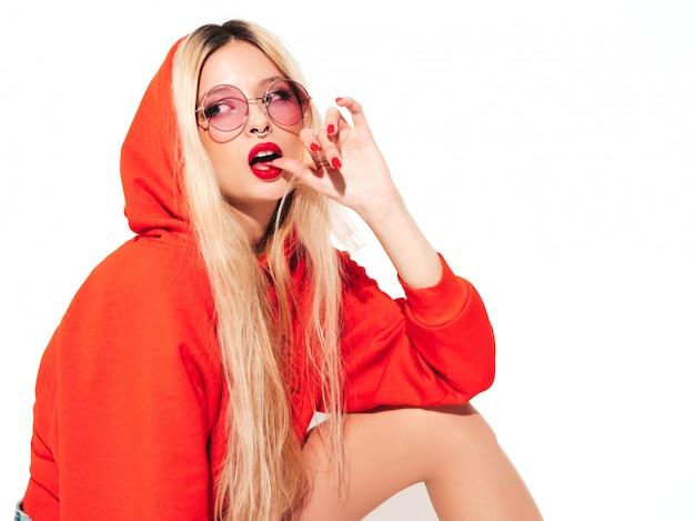 Портрет молодой красивой битник плохая девушка в модном красном балахоне и серьги в носу. позитивная модель с удовольствием. кусает палец