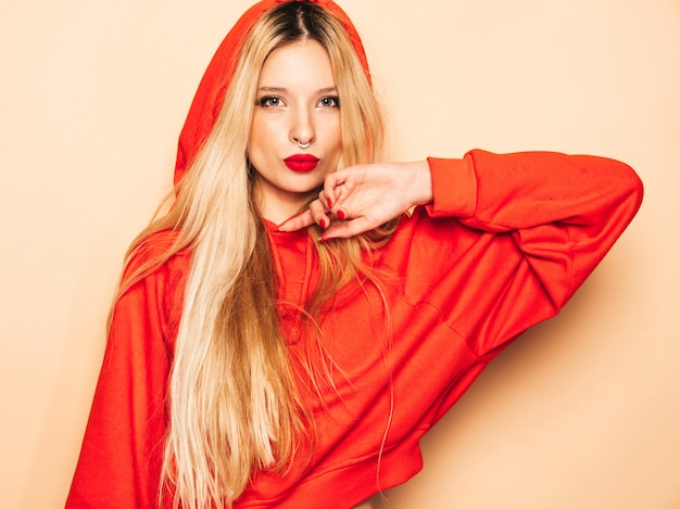 トレンディな赤いパーカーと彼女の鼻にイヤリングの若い美しい流行に敏感な悪い女の子の肖像画。楽しい肯定的なモデル