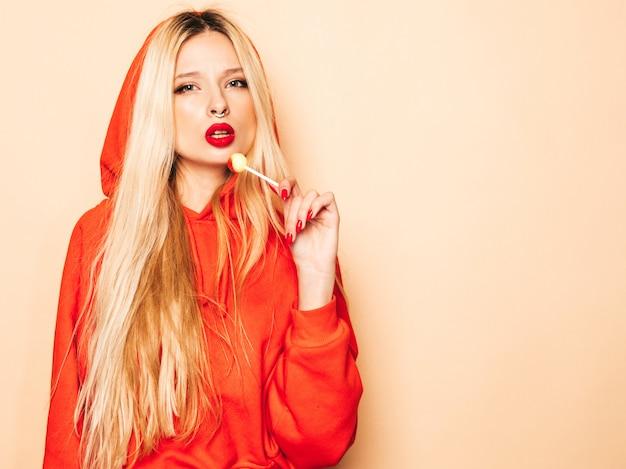 トレンディな赤いパーカーと彼女の鼻にイヤリングの若い美しい流行に敏感な悪い女の子の肖像画。丸い砂糖菓子を舐める肯定的なモデル