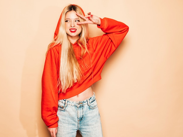 トレンディな赤いパーカーと彼女の鼻にイヤリングの若い美しい流行に敏感な悪い女の子の肖像画。肯定的なモデルはピースサインを示しています