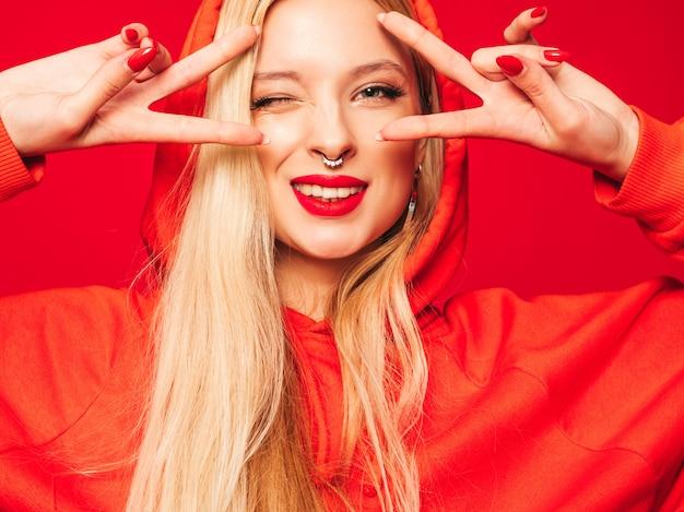 Портрет молодой красивой битник плохая девушка в модном красном балахоне и серьги в носу. позитивная модель показывает знак мира