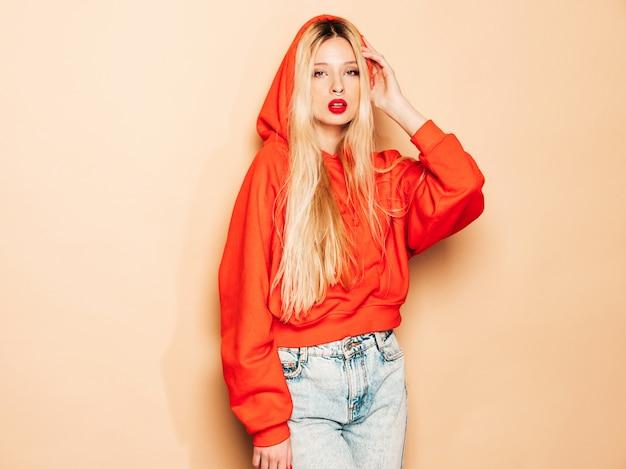 トレンディな赤いパーカーと彼女の鼻にイヤリングの若い美しい流行に敏感な悪い女の子の肖像画。ポジティブモデル