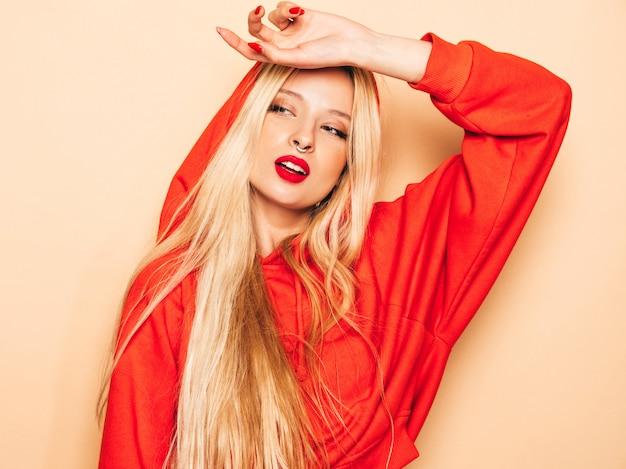 Портрет молодой красивой битник плохая девушка в модном красном балахоне и серьги в носу. позитивная модель