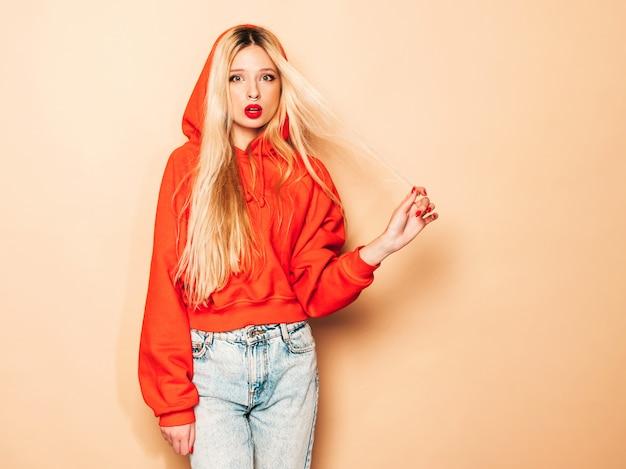 トレンディな赤いパーカーと彼女の鼻にピアスの若い美しい流行に敏感な悪い女の子の肖像画。セクシーな屈託のない金髪の女性がスタジオでポーズします。楽しい肯定的なモデル