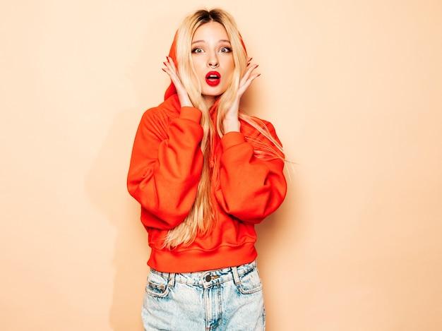 トレンディな赤いパーカーと彼女の鼻にイヤリングの若い美しい流行に敏感な悪い女の子の肖像画。ショックを受けて驚いた