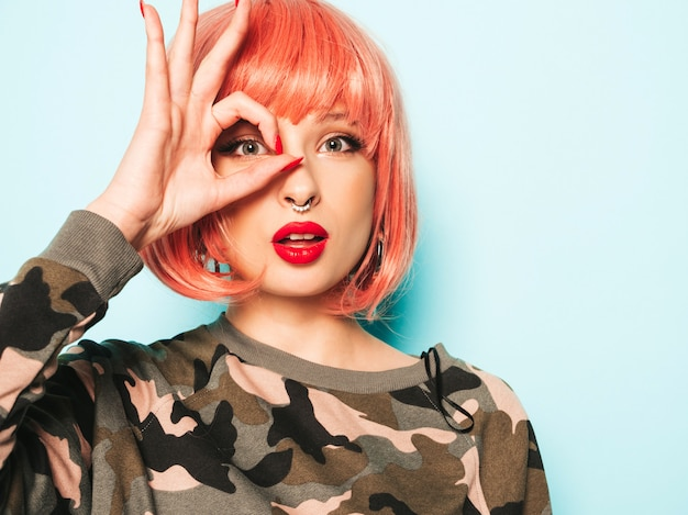 トレンディな赤い夏服と彼女の鼻にピアスの若い美しい流行に敏感な悪い女の子の肖像画。ピンクのかつらのスタジオでポーズをとってセクシーな屈託のない笑顔の女性。モデルは彼女の目を覆い、okの標識を示しています