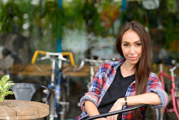 屋外の街の通りで若い美しい流行に敏感な女性の肖像画