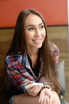 屋内のコーヒーショップでリラックスした若い美しい流行に敏感な女性の肖像画